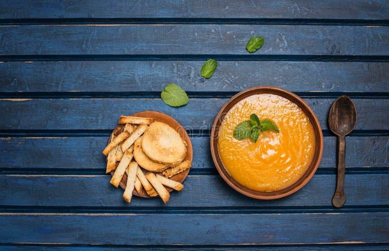 Pumpkin soup and organic pumpkins, top view, copy space. Seasonal autumn food spicy pumpkin soup with cream and pumpkin seeds. stock image