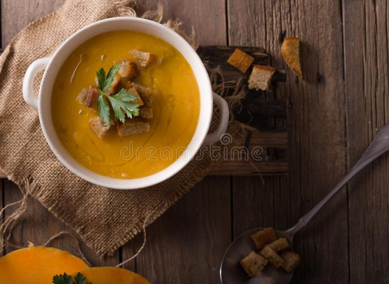 Pumpkin soup and organic pumpkins on wooden table. Seasonal autumn food - Spicy pumpkin soup in bowl. stock image