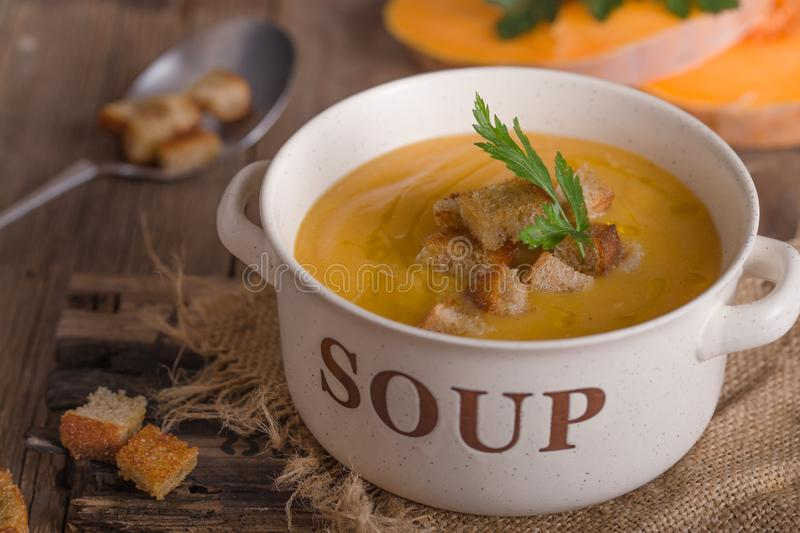 Pumpkin soup and organic pumpkins on wooden table. Seasonal autumn food - Spicy pumpkin soup in bowl. royalty free stock photos