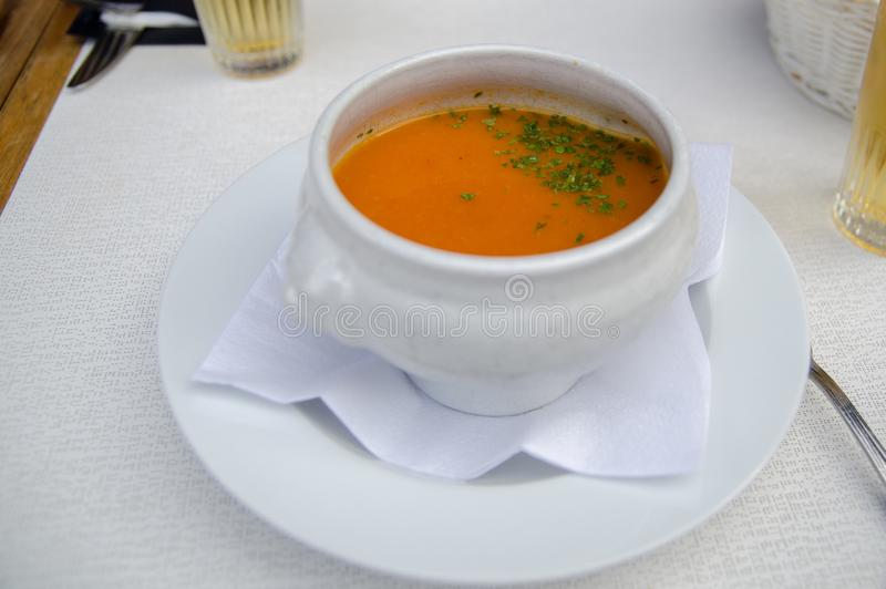 Pumpkin soup and parsley leaves in a white boil. At street cafe royalty free stock photography