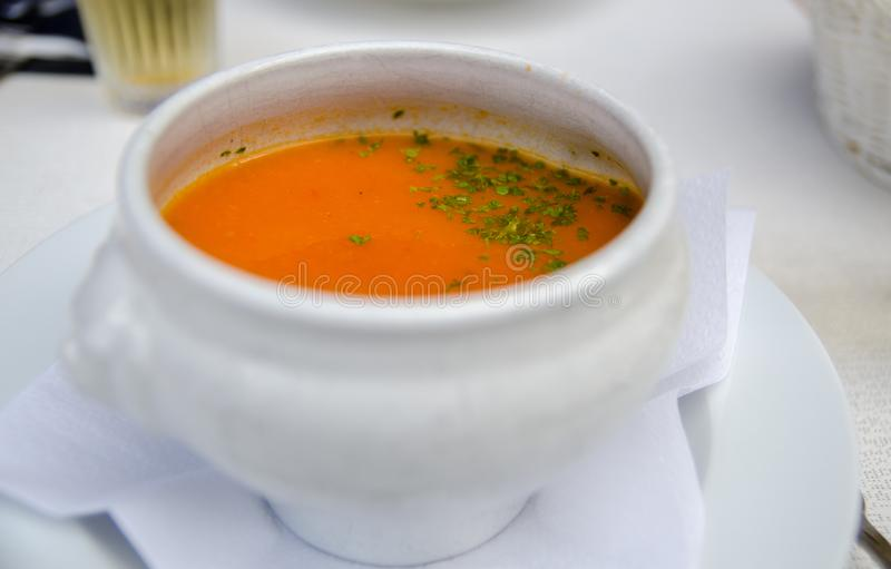 Pumpkin soup and parsley leaves in a white boil. At street cafe stock image