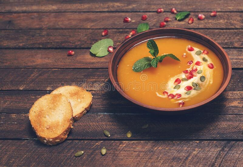 Pumpkin soup top view, copy space. Seasonal autumn food spicy pumpkin soup with cream and pumpkin and pomegranate seeds . Roasted royalty free stock photo