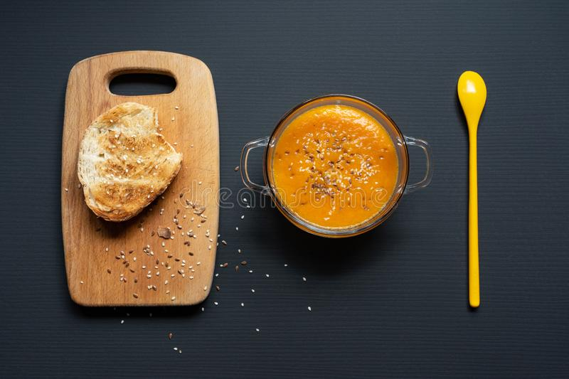 Pumpkin soup in a transparent glass plate, on a wooden board a piece of bread and a yellow spoon, sesame and flax seeds, top view stock image