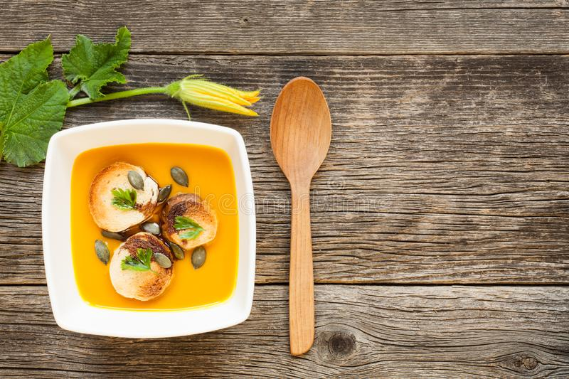 Pumpkin soup on a wooden table background stock photo