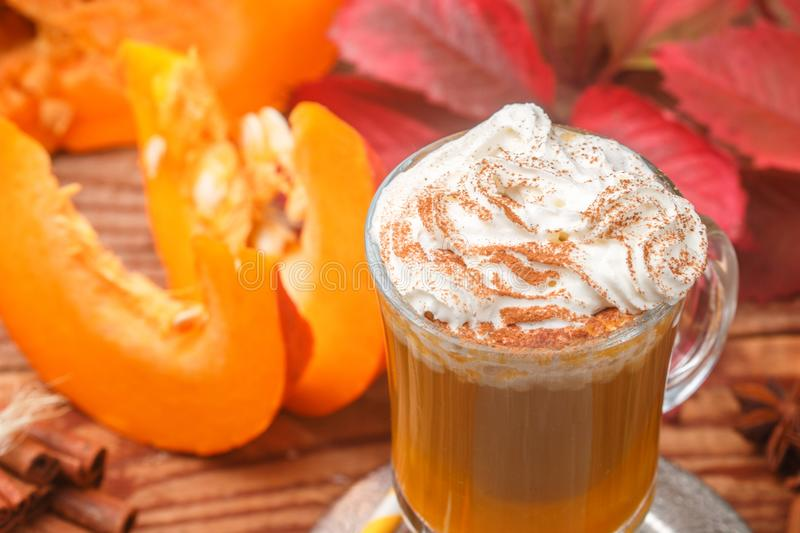 Pumpkin spice latte smoothie with whipped cream. And cinnamon in glass Cup on wooden background. Traditional autumn hot or cold beverage. Country style royalty free stock photography