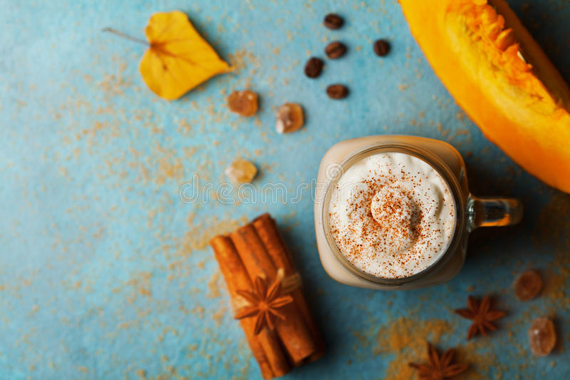 Pumpkin spiced latte or coffee in cup decorated cinnamon on turquoise vintage table top view. Autumn, fall or winter hot drink. Cozy breakfast royalty free stock images
