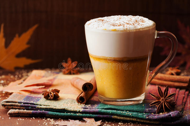 Pumpkin spiced latte or coffee in a glass on a rustic table. Autumn or winter hot drink. Pumpkin spiced latte or coffee in glass on a rustic table. Autumn or royalty free stock images