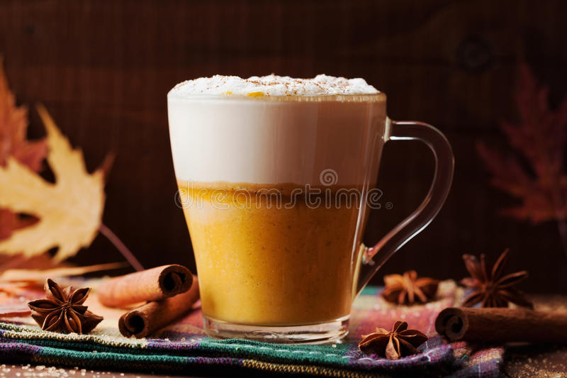 Pumpkin spiced latte or coffee in a glass on a wooden vintage table. Autumn or winter hot drink stock photography