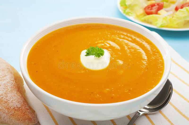 Pumpkin Soup Sweet Potato Carrot Salad Bread Copy Space. Pumpkin, sweet potato and carrot soup with a dollop of yoghurt, in a white bowl on a blue background stock photo