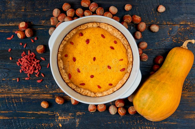 Pumpkin tart with goji berry in the baking dish decorated with hazelnuts on the black wooden background. Traditional autumn pie royalty free stock images