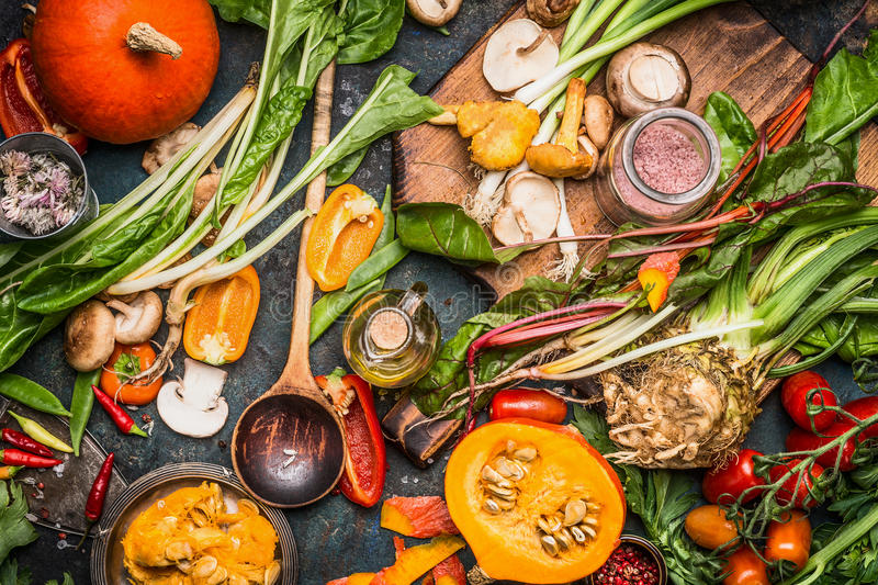 Pumpkin and Various autumn vegetables ingredients with wooden spoon for tasty vegetarian cooking. Top view royalty free stock photo