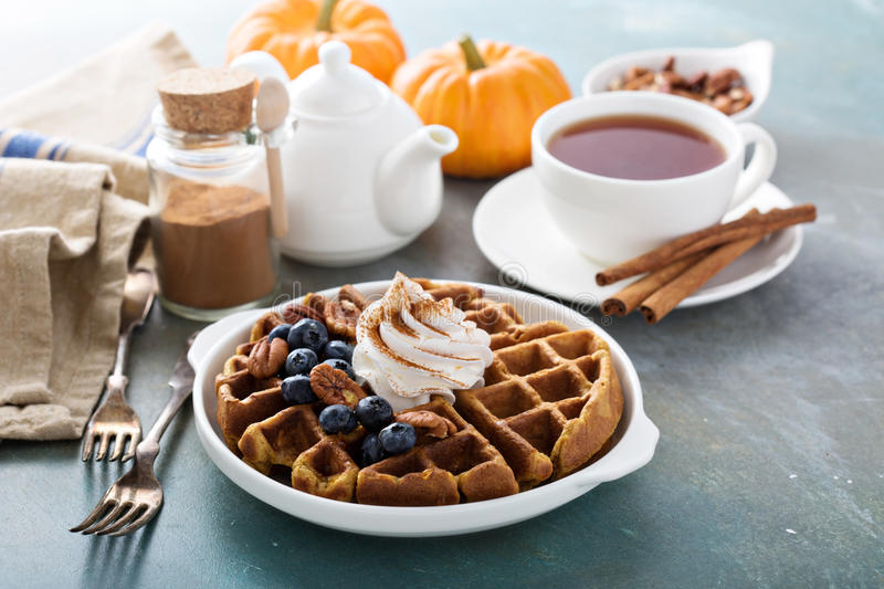 Pumpkin waffles with whipped cream for breakfast royalty free stock photography