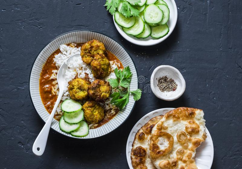 Pumpkin and zucchini fritters meatballs with rice and curry sauce. Healthy vegetarian food on dark background royalty free stock images