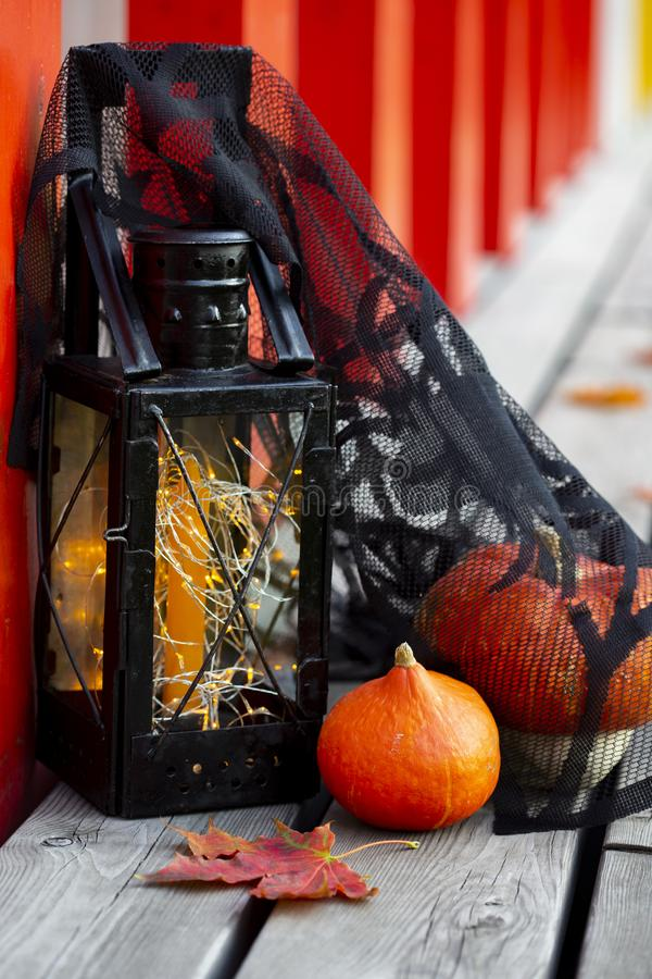 Pumpkins, autumn leaves and Halloween style vintage lamp with black cover. Orange candle and yellow lights on wooden surface royalty free stock photos