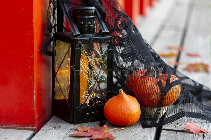 Pumpkins, autumn leaves and Halloween style vintage lamp with black cover. Orange candle and yellow lights on wooden surface stock image