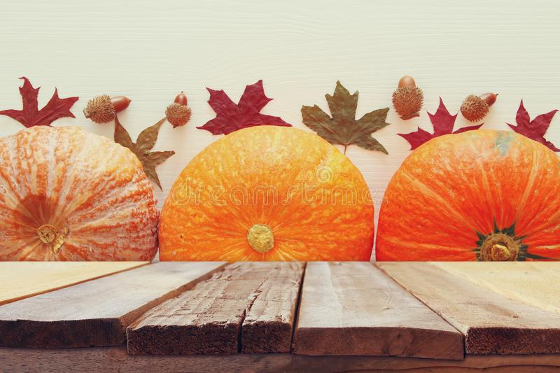 Pumpkins and autumn leaves on wooden background. thanksgiving and halloween concept royalty free stock photo