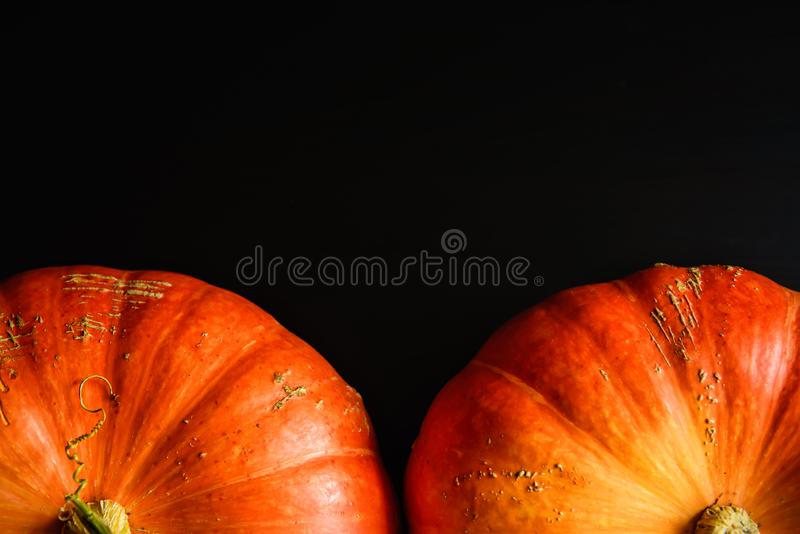 Pumpkins on black wooden table, top view. Halloween background with copy space. Autumn still life with orange pumpkins dark royalty free stock photography