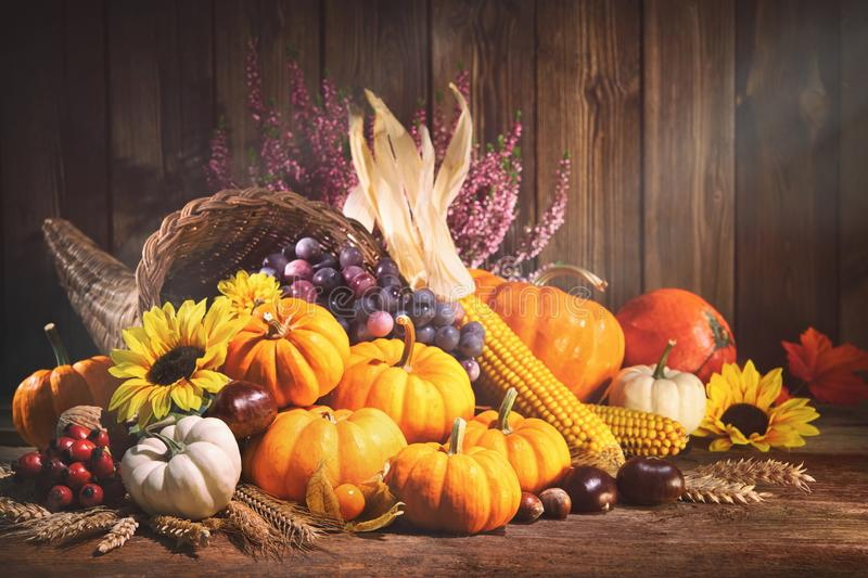 Pumpkins with fruits and falling leaves on rustic wooden table. Happy Thanksgiving. Decorative cornucopia with pumpkins, squash, fruits and falling leaves on royalty free stock photo