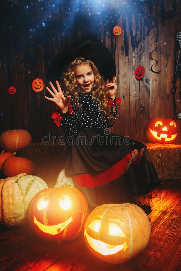 Among pumpkins at halloween. Cute curly girl in a costume of a witch holds pumpkin-lantern. Halloween party royalty free stock photos