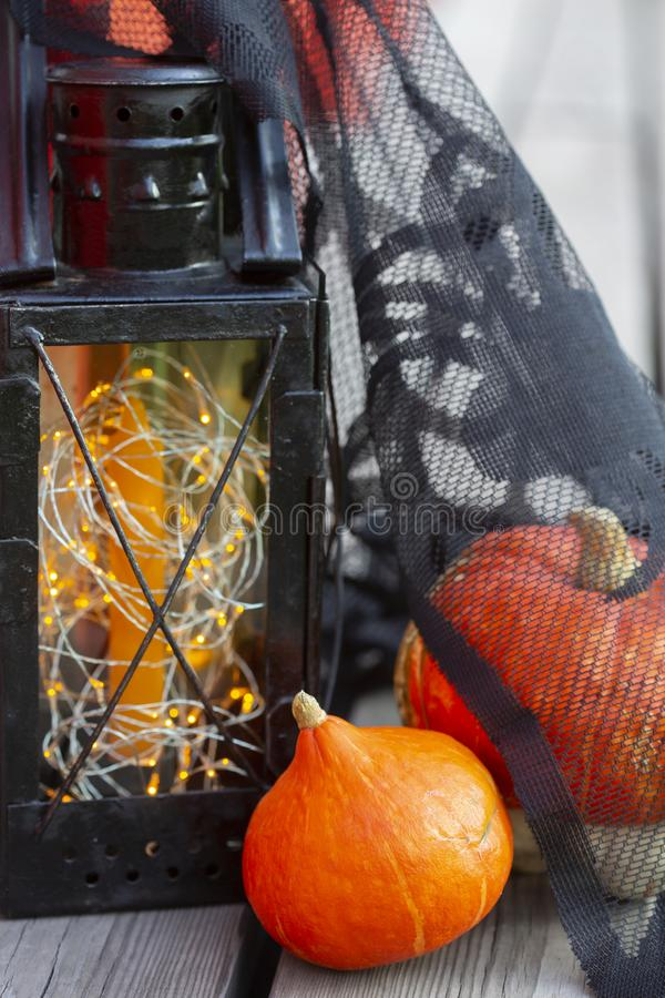 Pumpkins and Halloween style vintage lamp with black cover, orange candle and yellow lights. Pumpkins and Halloween style vintage lamp with black cover, orange stock image