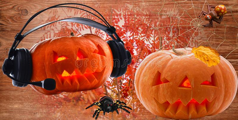 Pumpkins with burning eyes for the holiday of Halloween Day in the headphones and with a yellow leaf spiders on the October autumn. Pumpkins for the holiday of royalty free stock image