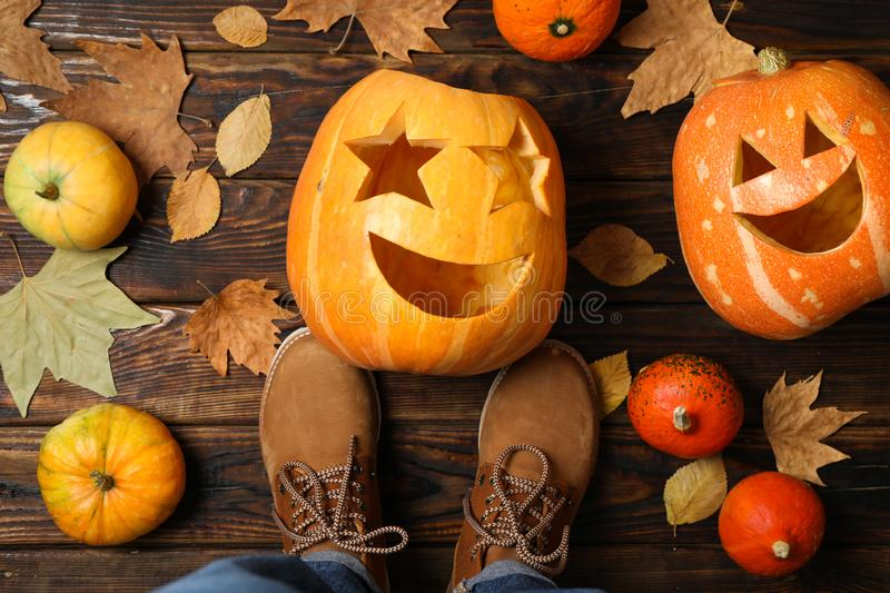 Pumpkins, leaves and legs in boots on wooden background royalty free stock photography