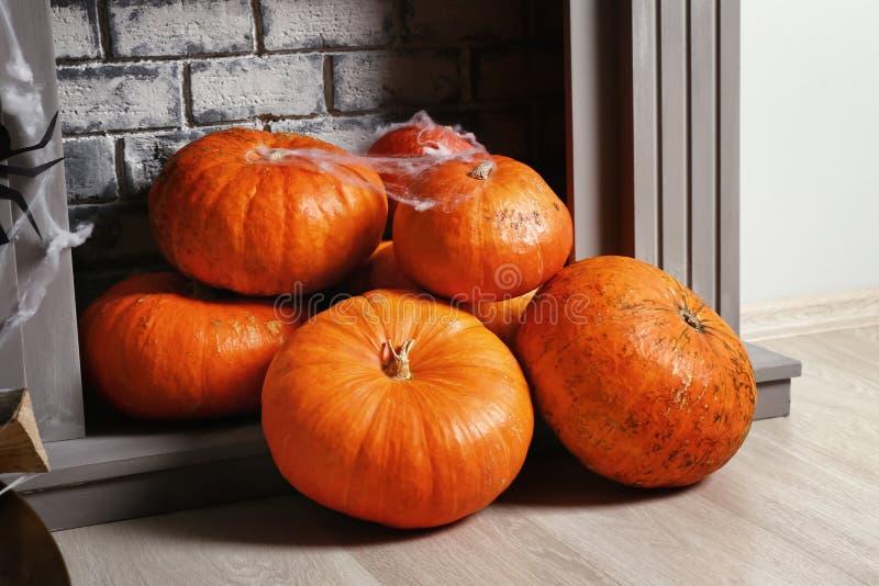 Pumpkins prepared for Halloween party near fireplace on floor stock photos