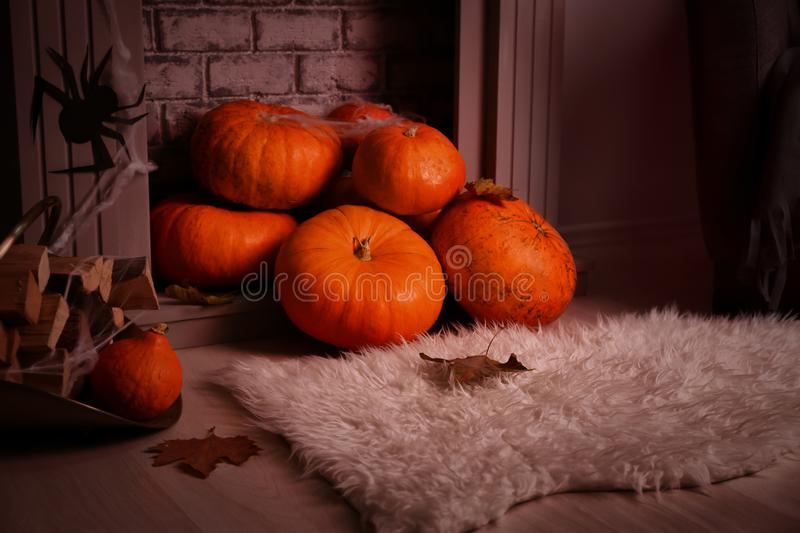 Pumpkins prepared for Halloween party near fireplace on floor royalty free stock photos