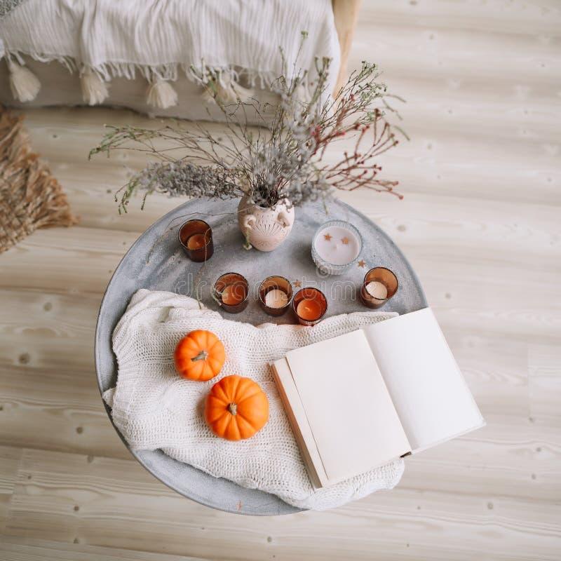 Pumpor, stearinljus, bok och torkade blommor med den varma filten Höst nedgång, allhelgonaafton, tacksägelsedagbegrepp Lekmanna-  royaltyfria foton