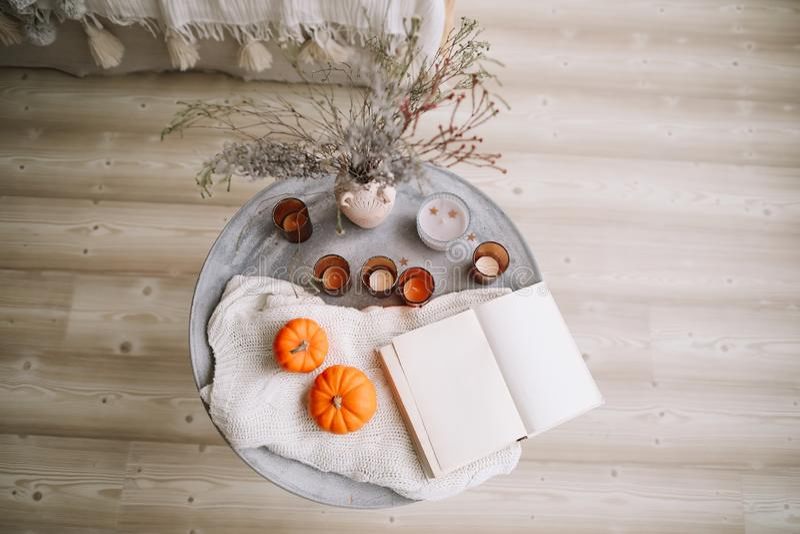Pumpor, stearinljus, bok och torkade blommor med den varma filten Höst nedgång, allhelgonaafton, tacksägelsedagbegrepp Lekmanna-  royaltyfri fotografi