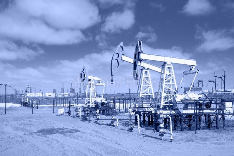 Pumpstålar på en oljefält tonat royaltyfria foton