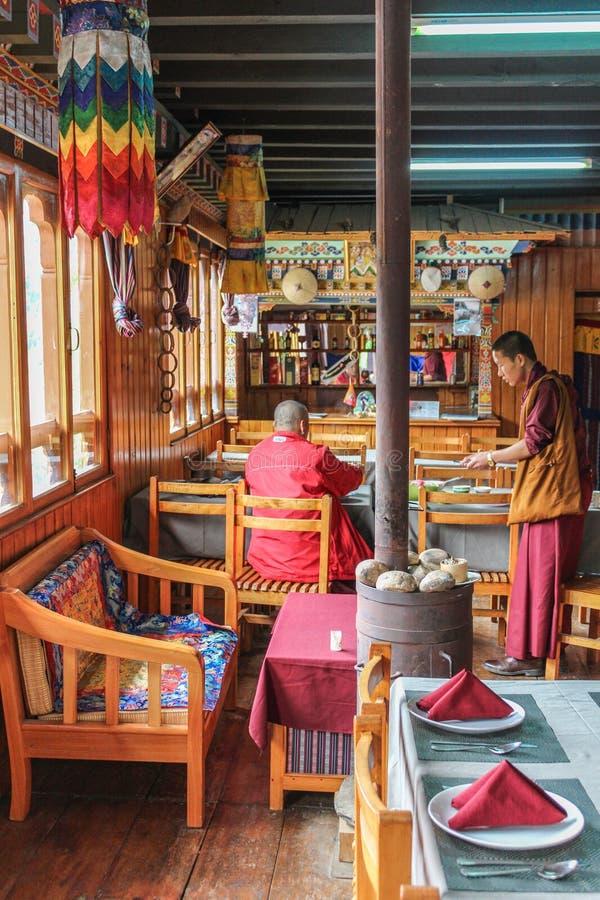 Punakha,不丹- 2016年9月12日:为一名顾客服务的传统服装的年轻侍者在一家餐馆在Punakha 免版税库存照片