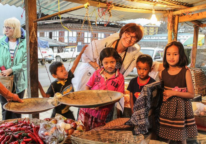 Punakha, Μπουτάν - 10 Σεπτεμβρίου 2016: Ευτυχής καυκάσια τοποθέτηση γυναικών με τα Bhutanese παιδιά σε bazaar με το κίτρινο φως σ στοκ εικόνες με δικαίωμα ελεύθερης χρήσης