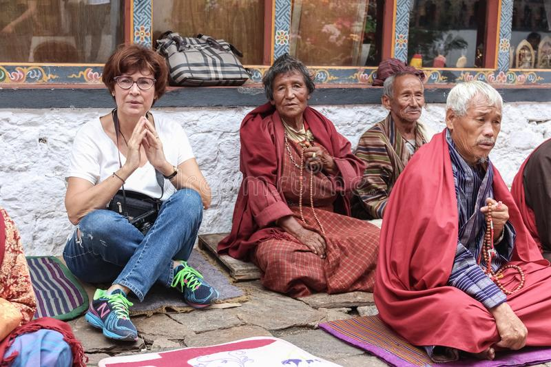 Punakha, Bhutan - September 11, 2016: Caucasian woman praying with Bhutanese people in Chimi Lhakhang monastery in Bhutan stock photography