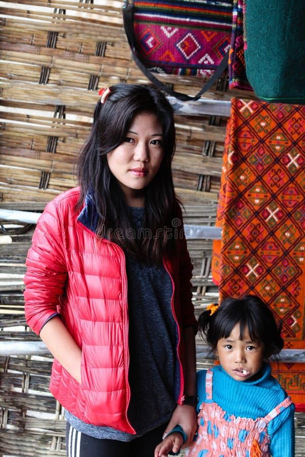 Punakha Bhutan - September 11, 2016: Stående av en bhutanesisk kvinna och en söt liten flicka royaltyfri bild