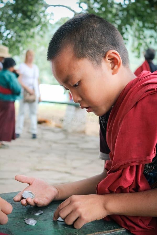 Punakha, Bhutan - 11 septembre 2016 : Jeune moine de Bhutanase comptant des pièces de monnaie sur sa main dans un monastère au Bh photos stock
