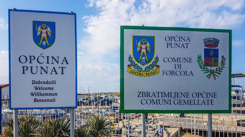 Punat - Welcome signs of Punat. Punat/Croatia-04302018: Two signs welcoming you to enter the territory of Punat. Both of them present the emblem of the city stock image