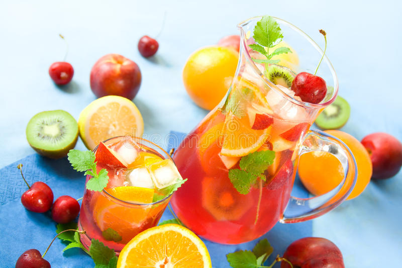 Punch. Jug and a drinking glass with colorful summer punch or lemonade and fruits royalty free stock photo