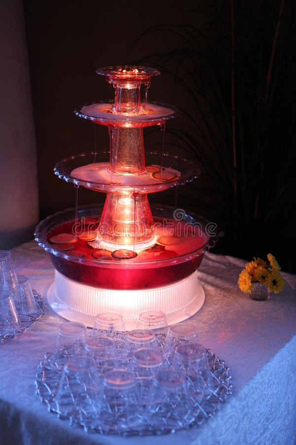 Punch Fountain. Red Punch cascading down a drink fountain in ambient lighting stock photography