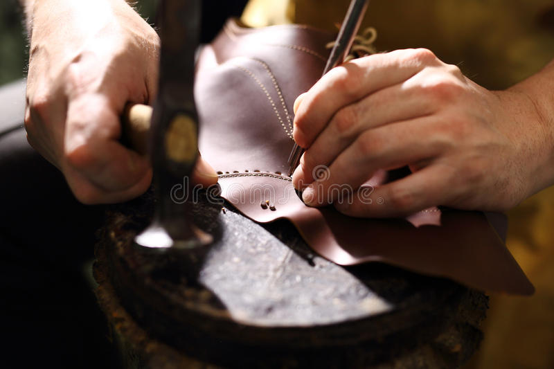 Punch leather for shoes. Shoemaker manually performs shoes in the studio craft stock photos