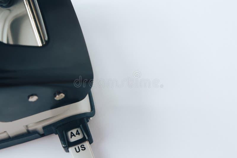 Puncher de agujero negro y gris del papel de la oficina en el fondo blanco fotografía de archivo libre de regalías