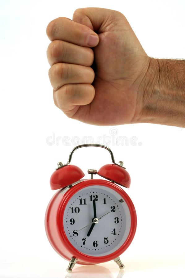Punching on an alarm clock on a white background stock photography