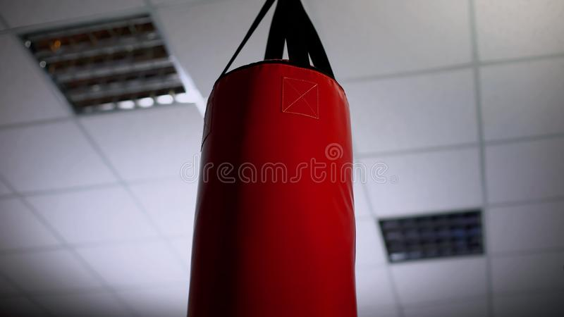 Punching bag under ceiling in office, overcoming business difficulties concept stock images