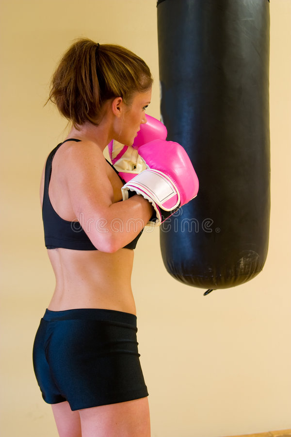 Punching With Pink Gloves 1. Beautiful boxing girl with pink gloves punching a bag royalty free stock photography
