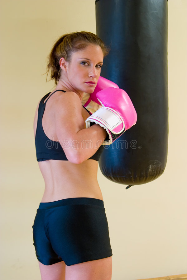 Punching With Pink Gloves 2. Beautiful boxing girl with pink gloves punching a bag royalty free stock photos
