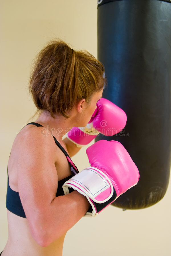 Punching With Pink Gloves 3. Beautiful boxing girl with pink gloves punching a bag stock photo