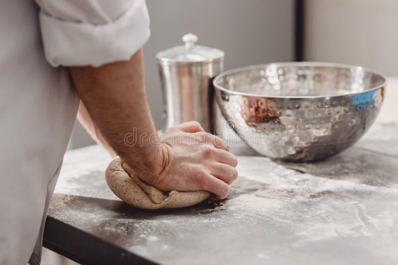 Punchs del panadero abajo de la pasta en la cocina en la panadería fotografía de archivo