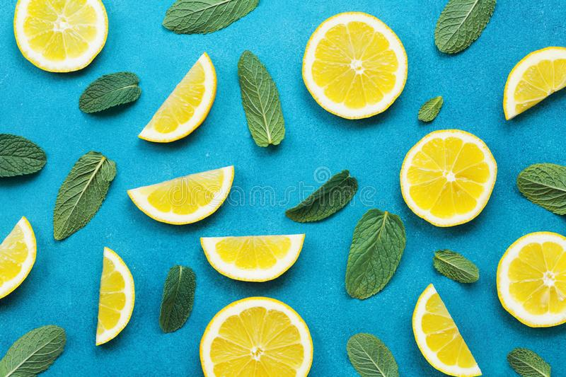 Punchy pastel background with lemon slices and mint leaves. Summer colorful pattern. Flat lay style. Punchy pastel background with lemon slices and mint leaves royalty free stock photo