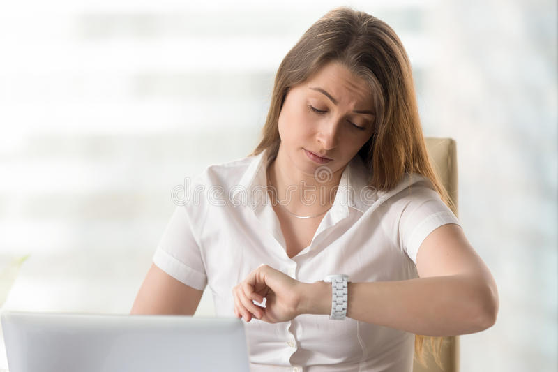 Punctual entrepreneur waiting important meeting. Serious businesswoman working on laptop in office and looking on wristwatch. Tired office worker checks royalty free stock photo