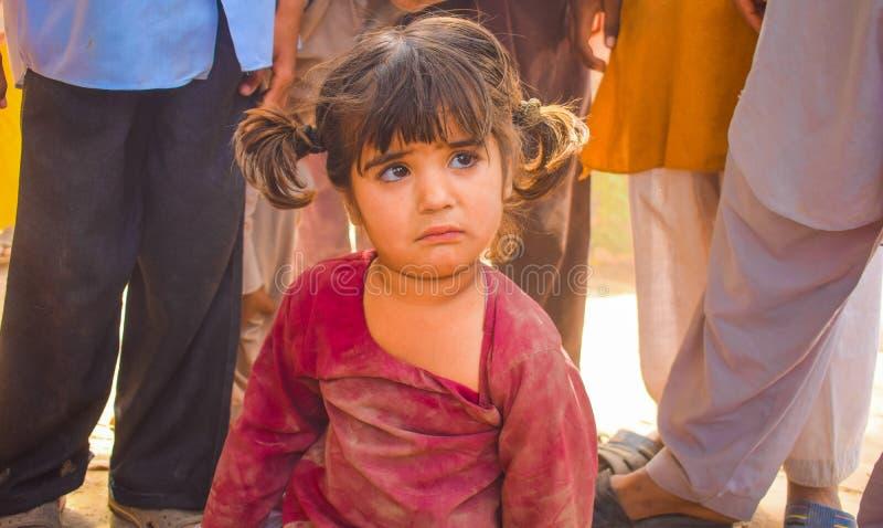 Pundżab, kwiecień 14,2019: zamyka w górę pakistańskiego małej dziewczynki obsiadania na ziemski patrzeć nieszczęśliwy zdjęcia royalty free